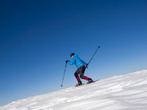 The man jumps in snowshoes in the mountains. Stock Photo