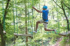 Man jumpswhile climbing in high rope course Stock Images