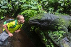 A man in the jungle next to the statue of a huge prehistoric lizard, a dinosaur.  stock photo