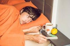 Man känslig förkylning och att ligga i sängen och dricker te och mäter t arkivfoton
