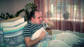 Man känsligt dåligt och att hosta och dricksvatten som hemma ligger i säng arkivfilmer