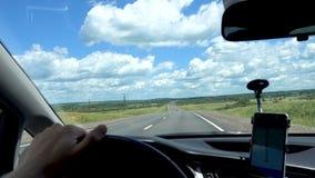 Man kör en bil på den hög hastigheten och rymmer hjulet med hans hand Väg blå himmel arkivfilmer