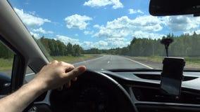 Man kör en bil på den hög hastigheten och rymmer hjulet med hans hand Väg blå himmel lager videofilmer