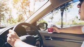 Man körning av bilen genom att använda en hand, medan rymma en kaffekopp i annan hand Arkivbild