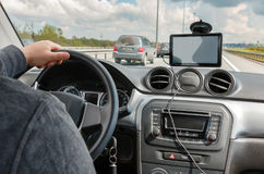 Man körning av bilen med händer på styrninghjulet och att använda GPS navigeringen arkivfoto