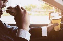 Man körning av bilen, medan rymma en kopp av kallt kaffe och äta hamburgaren royaltyfri bild