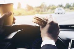 Man körning av bilen, medan rymma en kopp av kallt kaffe och äta hamburgaren Royaltyfri Fotografi
