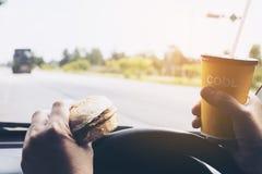 Man körning av bilen, medan rymma en kopp av kallt kaffe och äta hamburgaren arkivbilder
