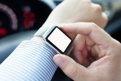 Man körning av bilen och av klockan med den isolerade skärmen på handen Royaltyfria Bilder