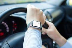 Man körning av bilen och av klockan med den isolerade skärmen på handen Arkivfoto