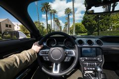 Man körning av den lyxiga bilen i Beverly Hills, Kalifornien på den varma sommardagen Lyxigt livsstilbegrepp arkivbild