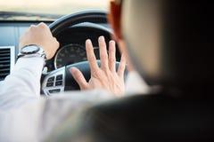 Man körning av en bil med handen på den horn- knappen royaltyfri foto