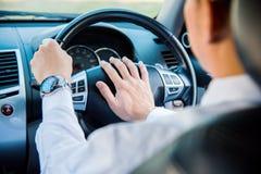 Man körning av en bil med handen på den horn- knappen arkivbilder