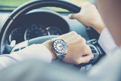 Man körning av en bil och att se klockan Arkivbilder