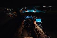 Man körning av en bil på nattstaden i biltrafik som jagar en annan bil Arkivfoto
