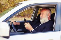 Man körning av hans bil och att se smartphonen fotografering för bildbyråer
