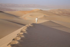 Man in kandura in a desert at sunrise Stock Photography