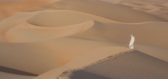 Man in kandura in a desert at sunrise Stock Photo