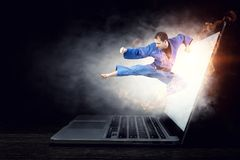 Man in kimono and glowing laptop. Mixed media. Man karate fighter jumping from laptop screen. Mixed media Stock Images