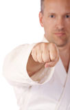 Karate Fist. Man in karate-gi in low DoF behind his fist Stock Photos