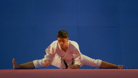 Man karate practitioner sitting in twine position on the floor while stretching his muscles during warm up stock video footage