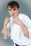 Man in karate suit and stance. Handsome young man with black belt in white martial art suit with raised fists in defensive position, studio background Stock Images