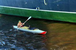 Man in a kayak floats next to the side of the ship Stock Photography