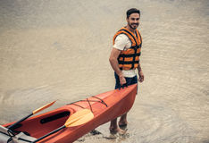 Man and kayak. Handsome young man in sea vest is looking at camera and smiling while pulling a kayak to the river to sail Royalty Free Stock Images