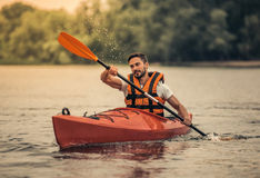 Man and kayak. Handsome young man in sea vest is smiling while sailing a kayak Royalty Free Stock Photo