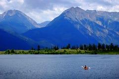 Man on Kayak on Lake Mountains Wilderness Paddling. On water Stock Photo