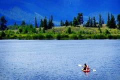 Man on Kayak on Lake Mountains Wilderness Paddling. On water Royalty Free Stock Photography