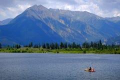 Man on Kayak on Lake Mountains Wilderness Paddling. On water Royalty Free Stock Photos