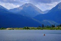 Man on Kayak on Lake Mountains Wilderness Paddling. On water Stock Image