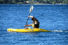 A man in kayak in a lake. People, family, men women and children kayaking in the lake deep blue water. Enjoing vacaciones, weekend, active sports. Sunny day stock photo