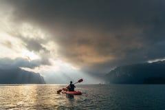 Man on kayak meetting sunrise on Cheow Lan Lake, Khao Sok national Park, Thailand royalty free stock photo