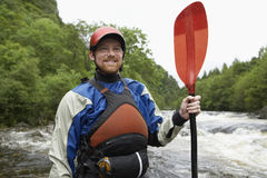 Man With Kayak Oar Against River. Portrait of a smiling man holding kayak oar against the river Royalty Free Stock Photos