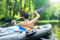 Man in kayak with oars. Kayaking on wild river. Active water sport on boat royalty free stock photo