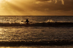Man in kayak on ocean with big waves at beautiful sunrise Stock Photos