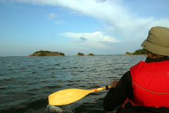Man in a kayak paddling toward an island, Scandinavia. Seascape on the Baltic Sea between the Aland Islands and Turku in Finland Royalty Free Stock Images
