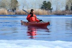 Man kayaking på en röd kajak på utfärder i natur 01 Arkivfoto