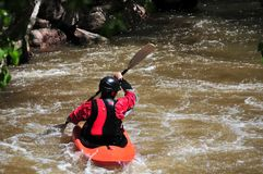 Man kayaking in rapids. Man in kayak on a swollen river in the spring Royalty Free Stock Image