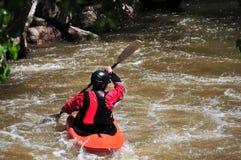 Man kayaking in rapids. Man in kayak on a swollen river in the spring royalty free stock image