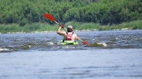 Man Kayaking on River at Sun stock photography
