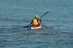 Man kayaking with a sea kayak. Adult man kayaking with a sea kayak in the ocean stock image