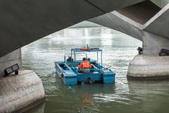 Man keep garbage boat on water under the bridge in Singapore. Man on keep garbage boat on water under the bridge in Singapore stock image