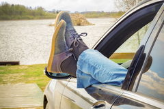 Man keep his legs through car window Royalty Free Stock Photo