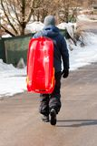 Boy carrying a red bobsleigh royalty free stock photo