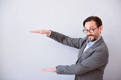 Man keeping hands like holding product Royalty Free Stock Image