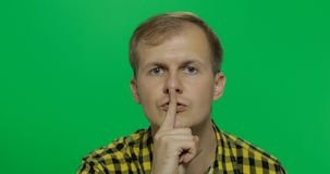 Man keeping a secret or asking for silence, serious face, obedience concept stock image