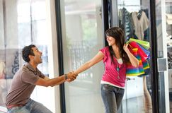 Man keeping a woman from entering a store Royalty Free Stock Image